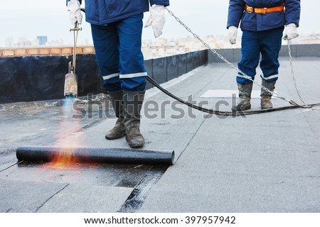 Flat roof installation. Heating and melting bitumen roofing felt  - stock photo