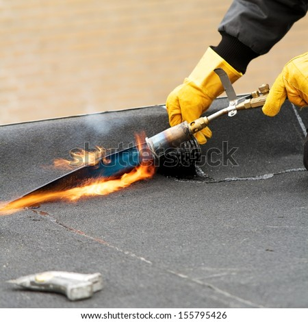 Flat roof repairing with roofing felt - stock photo