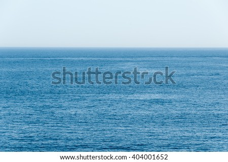 Flat, warm waters of a tropical sea in shades of deep blue, stretch unobstructed, all the way to the distant horizon background. - stock photo