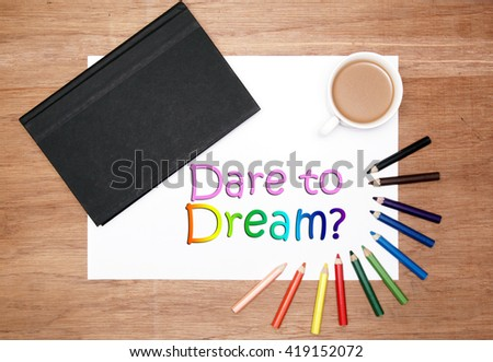 flatlaly of stationery. a black hard cover book, white drawing paper, a cup of coffee and colouring pencils. dare to dream text - stock photo