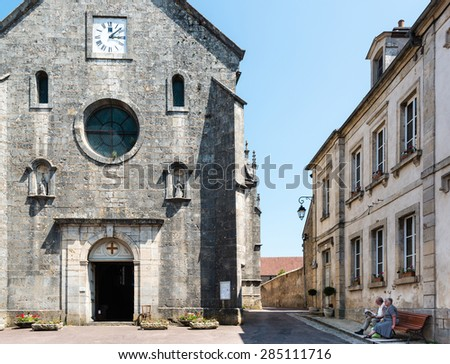 FLAVIGNY-SUR-OZERAIN, FRANCE - JUNE 6, 2015: A senior couple is sitting on a bench in front of the church Saint Genest in the small town of Flavigny-Sur-Ozerain, France. Flavigny is a medieval town - stock photo