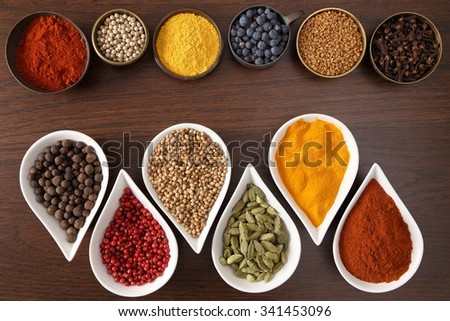Flavorful, colorful spices in metal and ceramic bowls on dark wooden background.