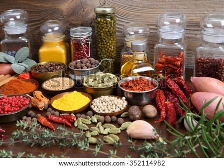 Flavorful, colorful spices in metal  bowls and glass bottles on dark wooden background. - stock photo
