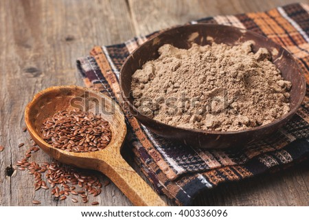 flax flour in a bowl, flax seeds  on a wooden background ( gluten-free diet ) - stock photo