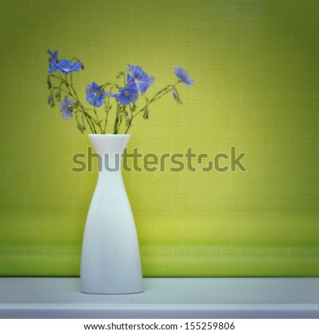 Flax flowers in a vase on a green background - stock photo
