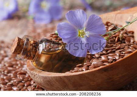 flax oil in a glass bottle, flowers and seeds in a wooden spoon macro horizontal  - stock photo