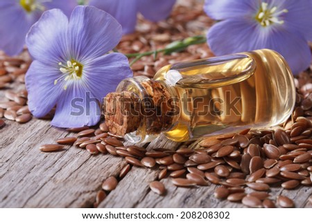 flax seeds, blue flowers and oil in a bottle on the table close-up horizontal  - stock photo