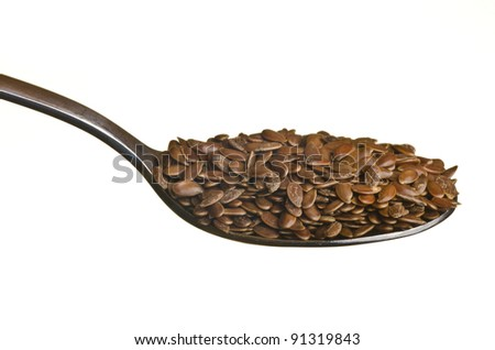 Flax seeds in a spoon isolated over white background - stock photo