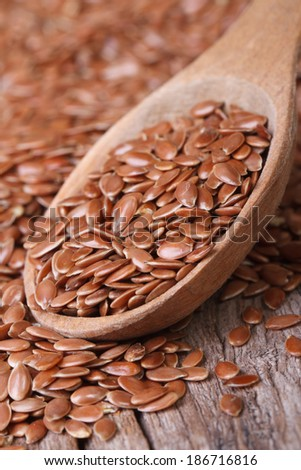 Flax seeds in a wooden spoon macro on a table. Vertical  - stock photo