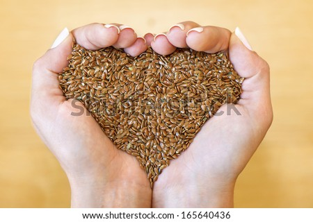 Flax seeds in woman's hands shaping heart - stock photo
