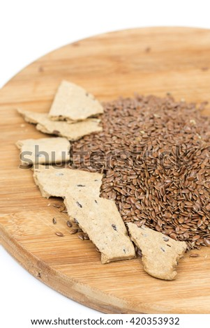 Flax seeds with flax snacks on the board. - stock photo