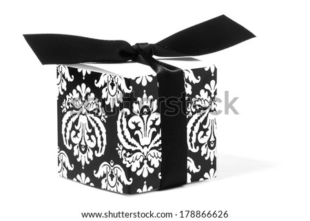 Fleur-de-lis designed gift box with attached black bow. White fleur-de-lis designs are on the black sides of the box. White background - stock photo