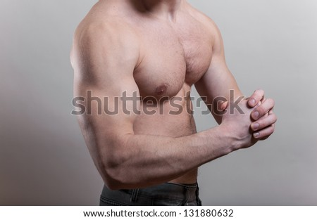 Flexed biceps. Very strong young guy over gray background in studio. - stock photo