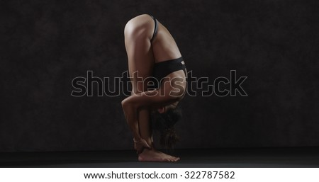 Flexible Asian woman bending over stretching legs - stock photo