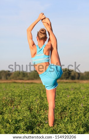 Flexible girl in green field