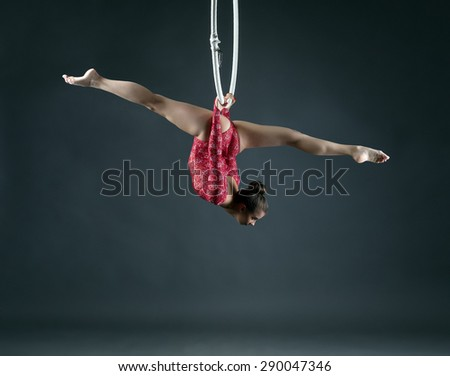 Flexible girl performs trick with hanging hoop - stock photo