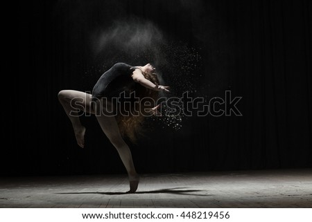 Flexible woman dancing with flour on black background