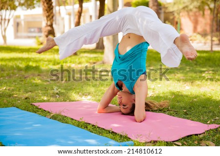 Flexible woman doing a headstand leg split while practicing yoga at a park - stock photo