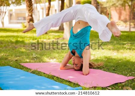flexible woman doing a headstand leg split while