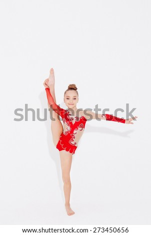 Flexible young girl in red dress doing split in stand position. Isolated on white - stock photo