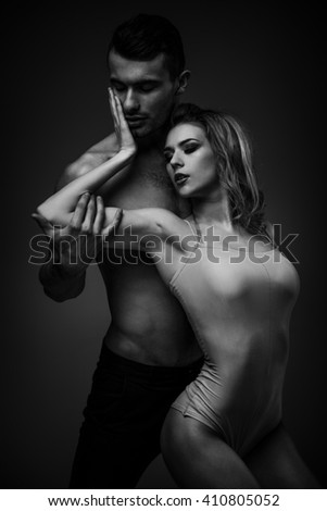 Flexible young modern acrobats couple posing in studio. Fashion portrait of attractive dancing couple. Man and woman. Passion. Love. perfect skin facial and make-up, blonde hair. black and white photo