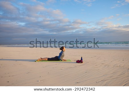 Flexible young woman performing the yoga pose called the cobra on her yoga mat on the beach at sunrise - stock photo