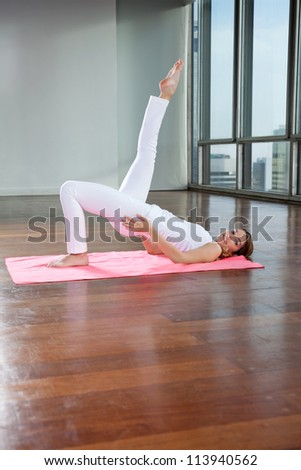 Flexible young woman practicing yoga exercise called Shoulder Stand on mat - stock photo