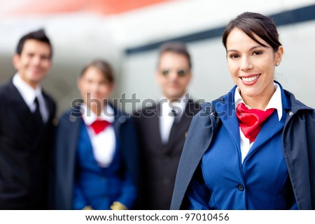 Flight attendant with cabin crew and an airplane at the background - stock photo
