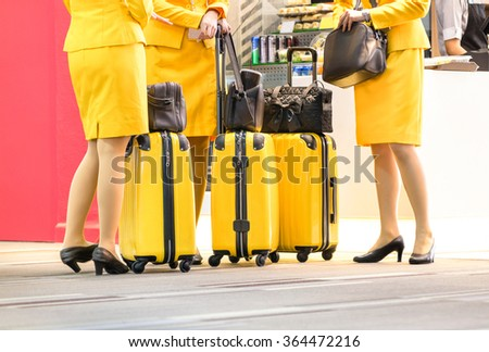 Flight attendants at international airport - Working travel concept with women on professional uniform at departure terminal gate ready for boarding - Shallow depth of field with main focus on luggage - stock photo