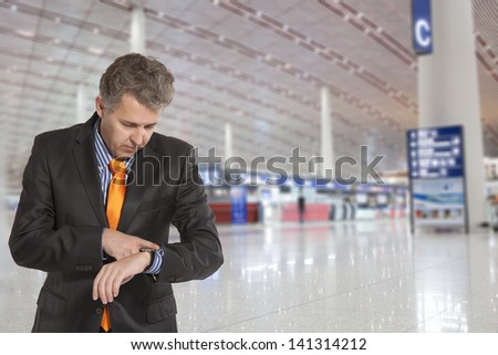 Flight delay. Businessman looking at his watch - stock photo