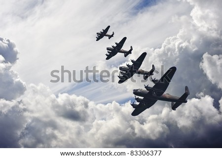 Flight formation of Battle of Britain World War Two consisting of Lancaster bombers banking right - stock photo