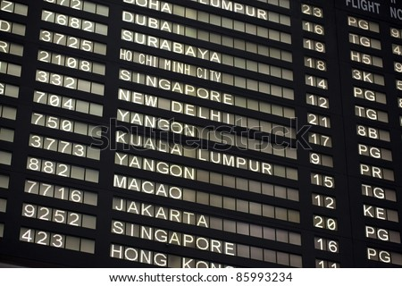 Flight information board in airport terminal - travel background - stock photo