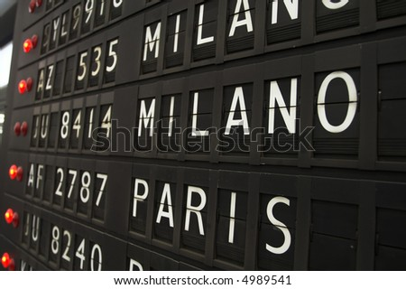 Flights info board on airport concept. Fashion cities Paris and Milano - stock photo