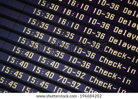 Flights information board in airport terminal - stock photo