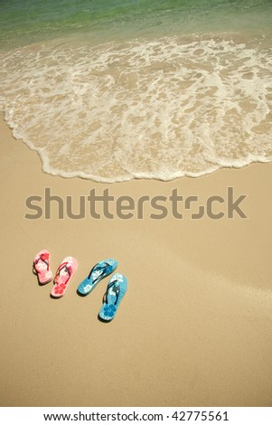 flip flop on the beach, with a blue sea, and sand - stock photo