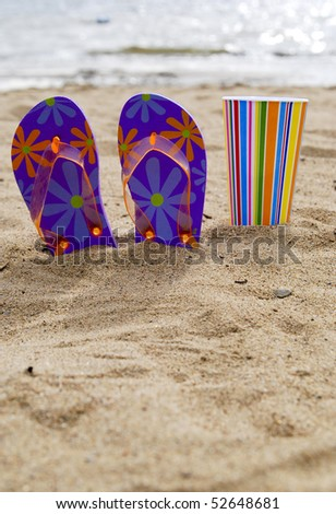 Flip flops and a colorful cup on a beach in the sun.