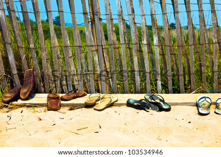 Flip flops and sandals lined up at the beach.  Old, well worn, not new - stock photo