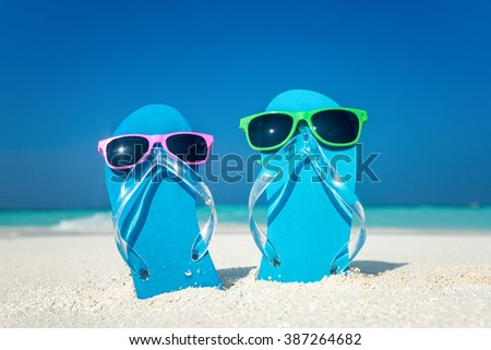 flip-flops and sunglasses by the sea - stock photo