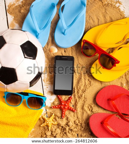 Flip flops, ball, phone, seashell and starfish with tropical flowers on sandy beach  - stock photo