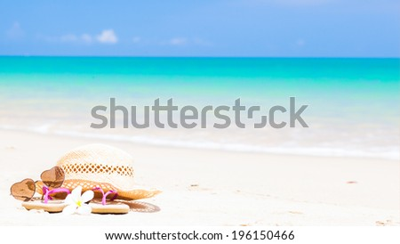 flip flops, heart-shaped sunglasses, straw hat and frangipani on tropical beach - stock photo