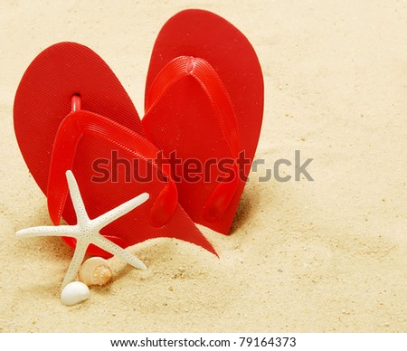 Flip-flops on a sandy beach with shells and a starfish - stock photo