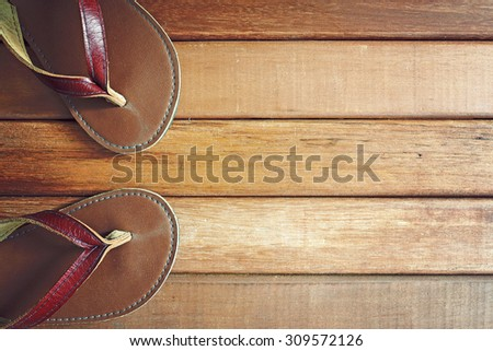 Flip flops on old wooden background. Top view with copy space. - stock photo