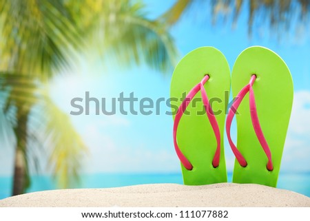 Flip-flops on sand beach. - stock photo