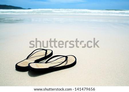 Flip flops on the sand on paradise beach - stock photo