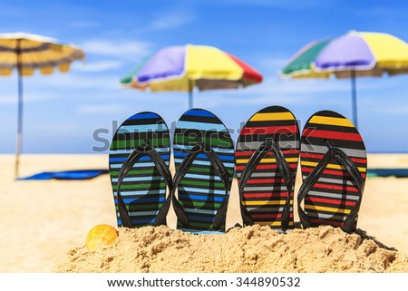 Flip flops on the sandy beach with blue sea and sky