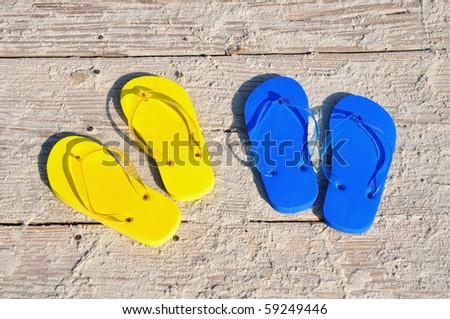Flip flops on wooden boardwalk - stock photo