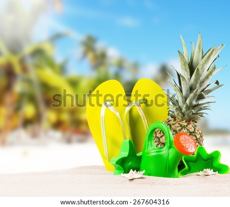 flip-flops, sand cake children  with tropical beach background, summer accessories - stock photo