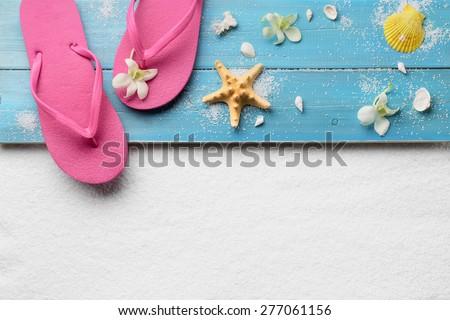 Flip-flops with seashells on sand beach - stock photo