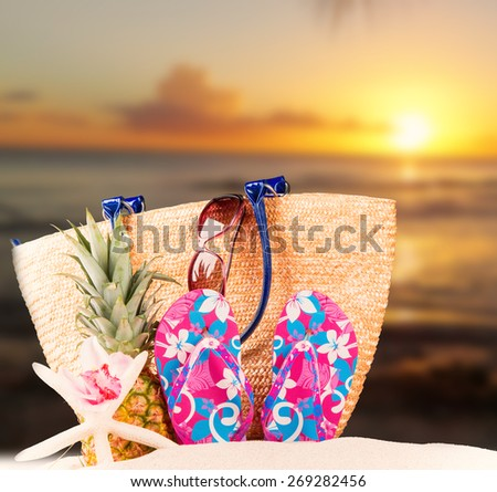 flip-flops with tropical beach background, sun set, summer accessories - stock photo