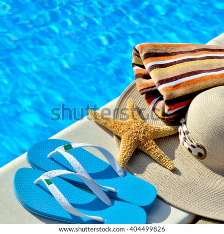 Flip-flops, woman beach hat and bright towel on against blue swimming pool.